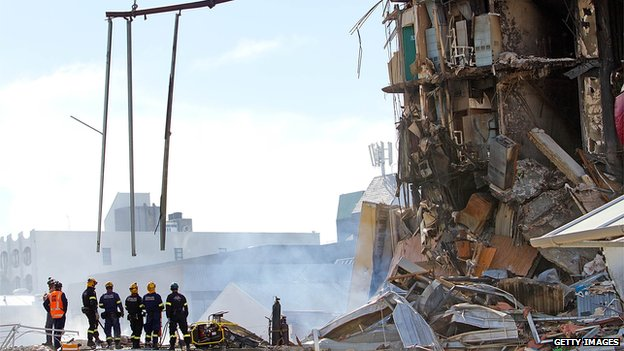 Rescuers stand at the smoking ruins of a building in Christchurch, New Zealand on 24 February, 2011