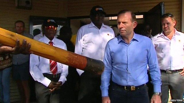 Tony Abbott watches a man play a didgeridoo as he arrives in northeast Arnhem Land