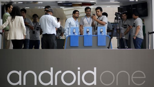 Visitors look at Android One-based mobiles after its launch in New Delhi