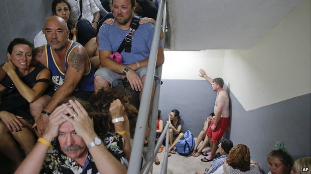 Tourists line the stairs of a service area after their shelter was destroyed by winds in Los Cabos, Mexico