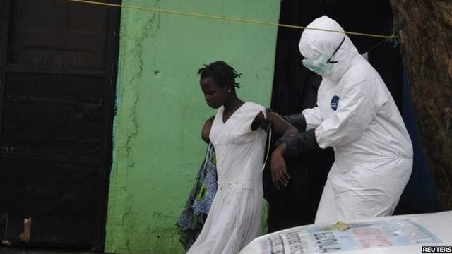 A woman and an Ebola health worker in a protective suit