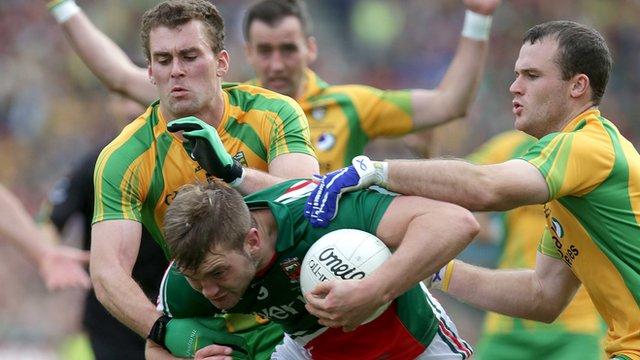Eamon and Neil McGee tackle Mayo's Aiden O'Shea