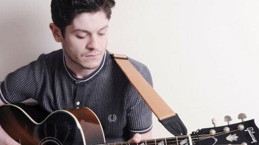 Mae Iwan yn dal i gael amser yn rhywle i afael yn ei gitar!