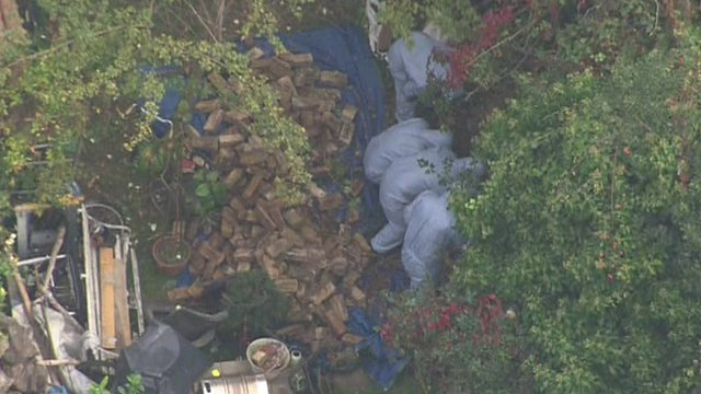 Forensic police officers search garden of suspect Arnis Zakalns's house in Ealing