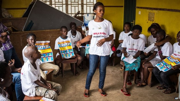 A charity worker educates children on how to prevent and identify the Ebola virus in their communities at Freetown, Sierra Leone