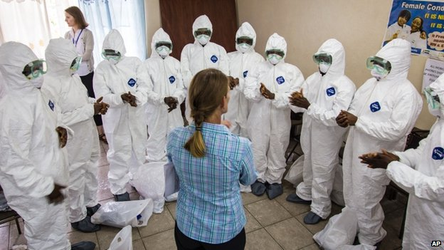 A World Health Organisation worker, (centre) trains nurses to use Ebola protective gear in Freetown, Sierra Leone (18 September 2014)