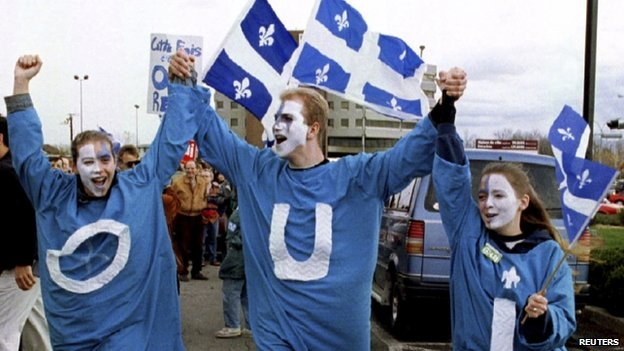 """Young """"YES"""" supporters, wearing frocks with the French word """"OUI"""", walk outside a rally in Quebec City, in this 29 October 1995 file picture."""