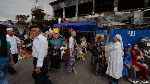 Uighur traders beside a burnt out market building at the main bazaar in Turpan, Xinjiang region, on 27 June 2013