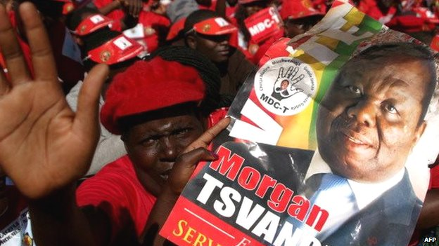 A supporter of the Movement for Democratic Change's Morgan Tsvangirai holds his portrait as they attend a campaign rally in Harare - July 2013