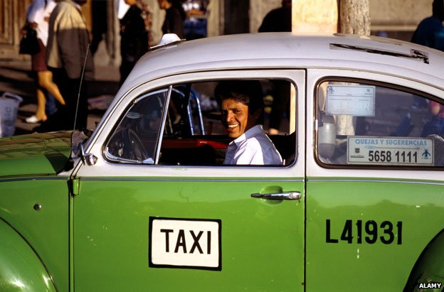 Taxi driver in one of Mexico City's distinctive green VW beetles