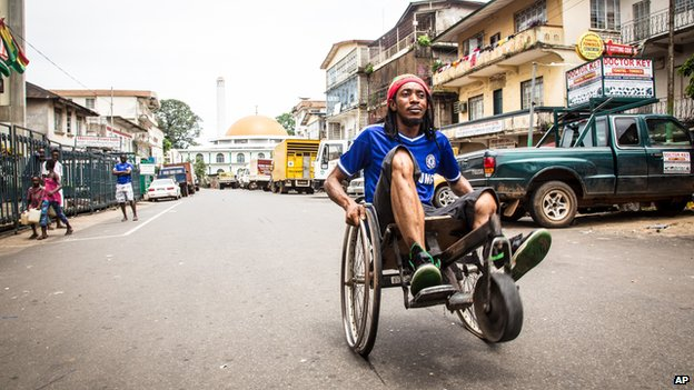 A man travels along a street in his wheelchair during a three-day lockdown to prevent the spread of the Ebola virus in Freetown, Sierra Leone, Sunday, Sept. 21, 2014