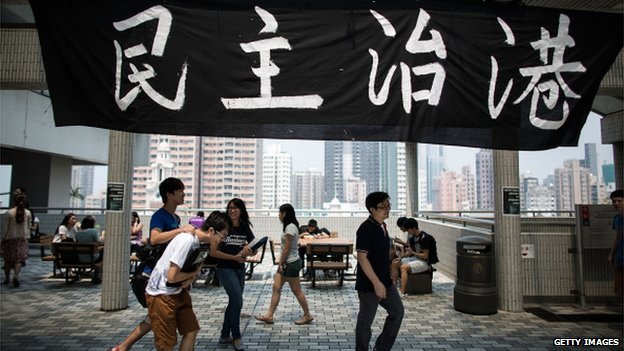 Students of The University of Hong Kong gather in front of a banner with Chinese characters that read ''Democracy in Hong Kong'' at its Sun Yat-sen Place at campus on 19 September 2014 in Hong Kong.