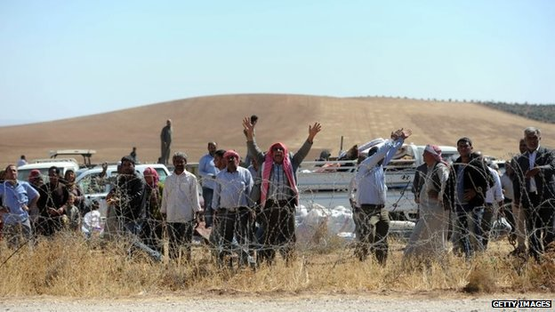 Syrian refugees wait to cross into Turkey at the border near the south-eastern town of Suruc in Sanliurfa province, Turkey, 22 September 2014