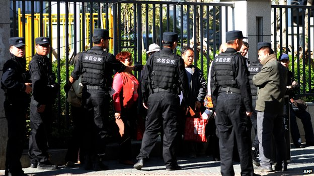 Chinese police ask a group of people who were denied entry to the Urumqi Intermediate People's court, to leave as the trial of Ilham Tohti