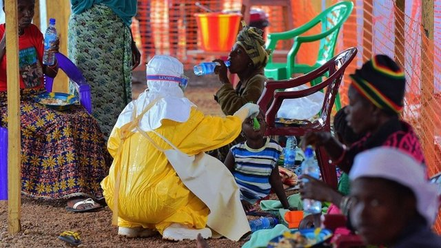 An MSF medical worker feeds an Ebola child victim