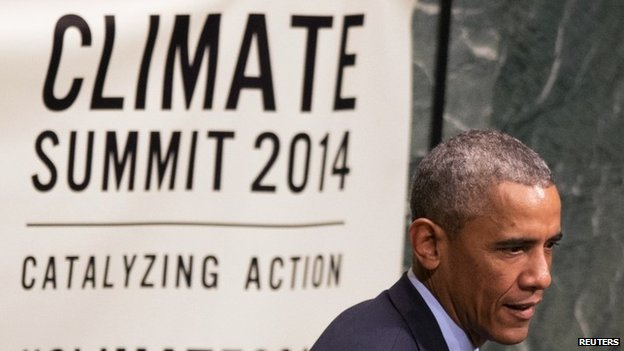 US President Barack Obama walks past a sign before speaking at the Climate Summit at the UN headquarters in New York (23 September 2014)