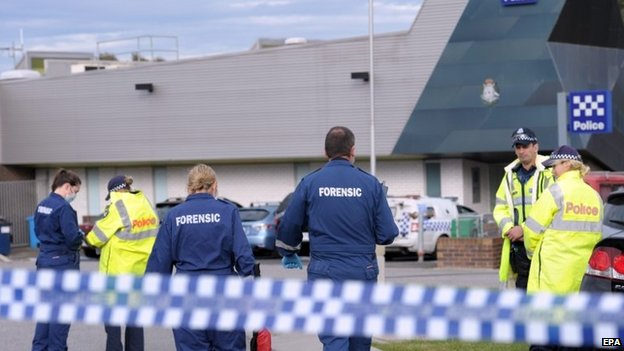 Police and forensic officers investigate the scene of a fatal shooting of an 18-year-old man at Endeavour Hills Police Station in Melbourne, Victoria, Australia, on 24 September 2014