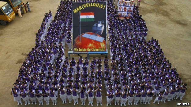 """Students pose in a group with banners featuring Mars and Indian Space Research Organization (ISRO) scientists (R) as they celebrate India""""s Mars orbiter successfully entering the red planet""""s orbit, at a school in the southern Indian city of Chennai September 24, 2014."""