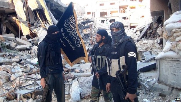 Al-Nusra Front members stand beside wrecked buildings in the Yarmouk Palestinian refugee camp in the south of Damascus (24 September 2014)