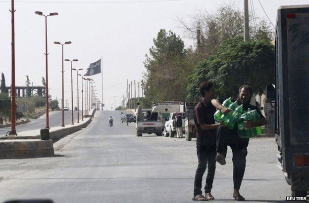 Residents collect goods in Tel Abyad, a Syrian town close to the Turkish border, as an Islamic State flag flutters from a post, 24 September