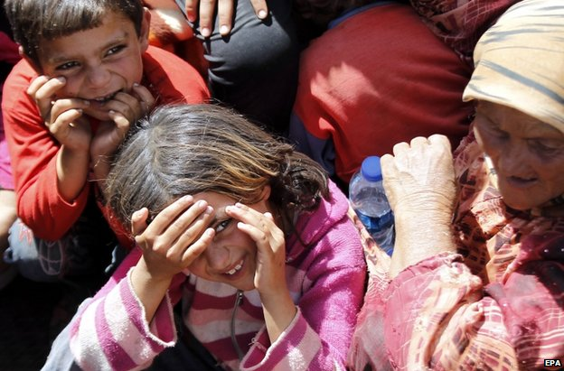 Syrian refugees wait at the Syrian-Turkish border near Sanliurfa, 25 September