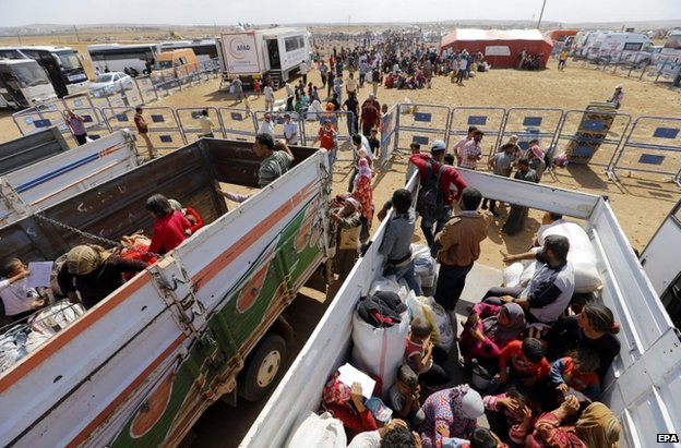 A Syrian refugee family load their belongings on to a lorry near the Syrian-Turkish border in Sanliurfa, 25 September
