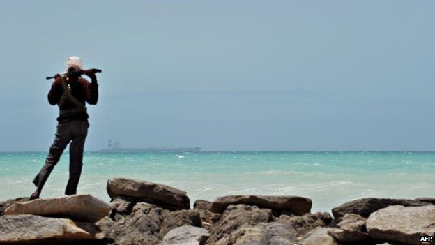 A pirate stands on a rocky outcrop on the coast in Hobyo in central Somalia, on 20 August 2010