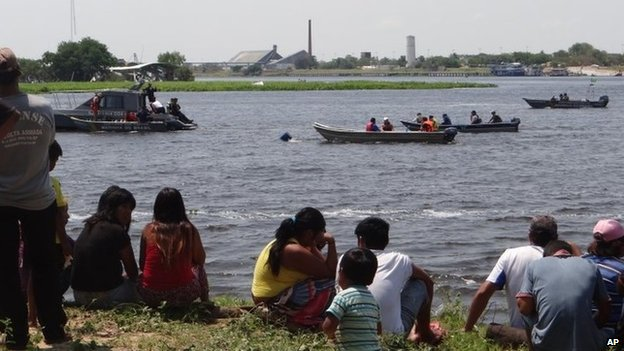 Onlookers follow River Paraguay rescue work, 25 Sep 14
