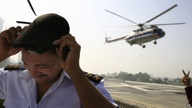 An Egyptian policeman takes cover as a helicopter transports former President Hosni Mubarak from the Maadi Military Hospital  to the Cairo court (27 September 2014)