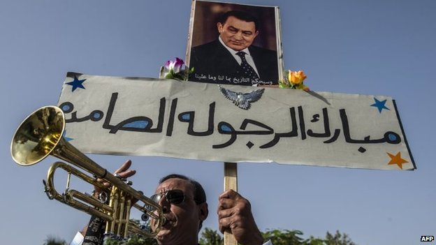 An Egyptian man holds a portrait of former President Hosni Mubarak as he expresses his support outside the Maadi military hospital in Cairo (27 September 2014)