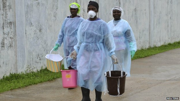 Health workers carry buckets of disinfectant at the newly-constructed Island Clinic and Ebola treatment centre in Monrovia, Liberia, on 25 September 2014.