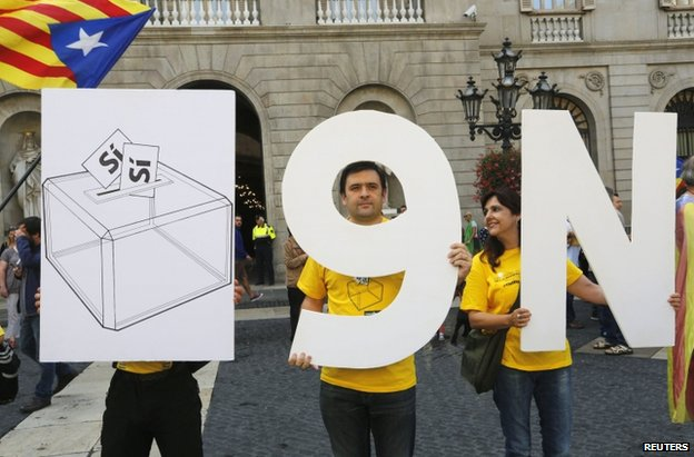 Catalan separatists hold placards in Barcelona to promote the proposed 9 November vote, 27 September