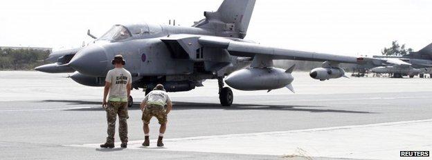 Servicemen stand near a Tornado jet as it prepares to take off