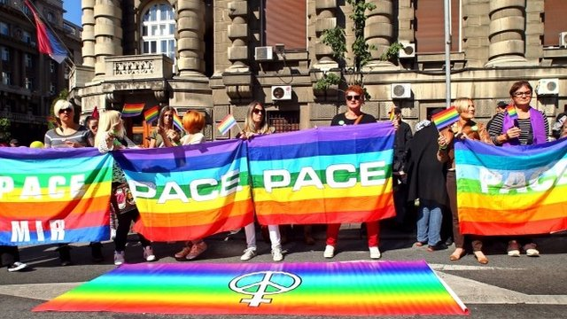 Gay rights activists holding a rainbow flag during a gay rights rally in downtown Belgrade