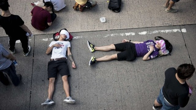 People sleep on the street as a large group of protesters block off Nathan Road, a major route through the heart of the Kowloon district of Hong Kong, on September 29, 2014