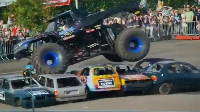 Monster truck driving over several empty cars