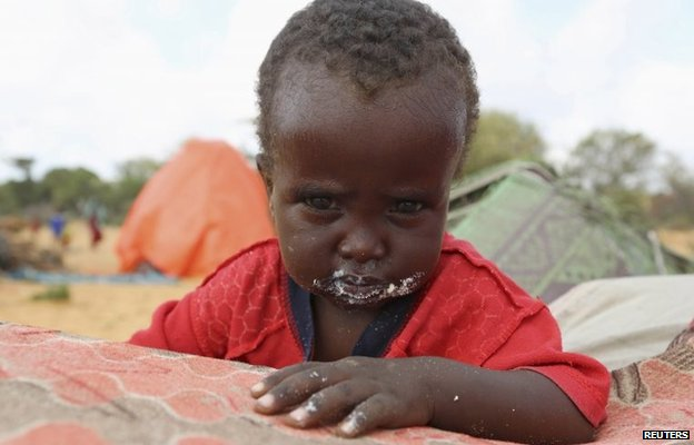 """A displaced child stands outside the family""""s temporary dwelling after fleeing famine in the Marka Lower Shebbele regions to the capital Mogadishu, September 20, 2014."""