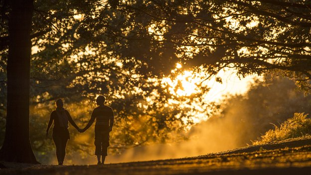 A couple walk through Richmond Park at sunset on September 12