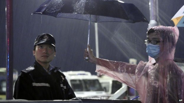 A young pro-democracy demonstrator holds an umbrella for a police officer during a demonstration in Hong Kong on 30 September 2014.
