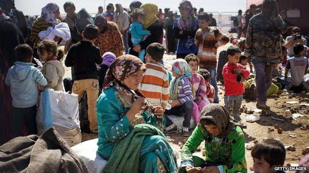 Syrian Kurds wait with their belongings before crossing into Turkey near Kobane (30 September 2014)