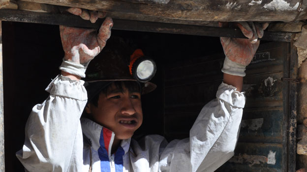 Young miner, Luis, chews coca before work