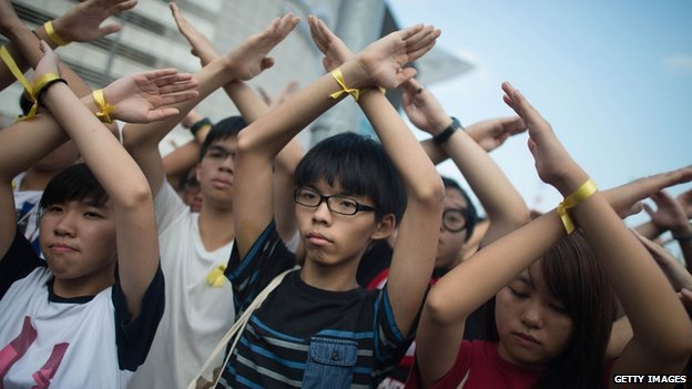 Student pro-democracy group Scholarism convenor Joshua Wong (C) makes a gesture at the Flag Raising Ceremony on 1 October 2014 in Hong Kong