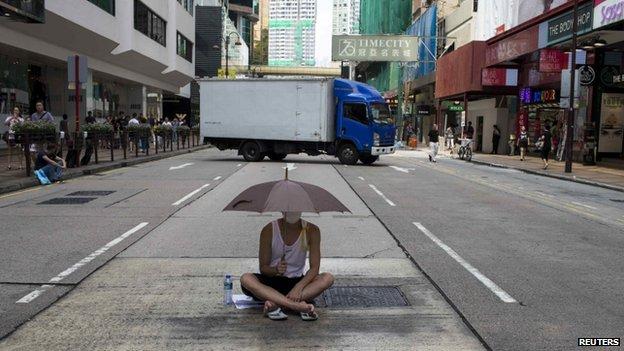 A protester sits under an umbrella as he attends a rally along a main street at Hong Kong's shopping district Tsim Sha Tsui October 1, 2014.