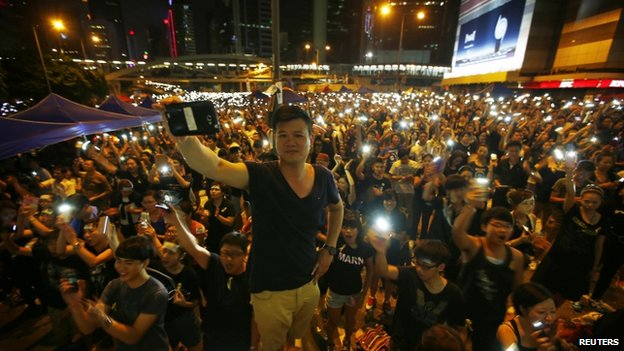 Protesters turn on their mobile phone flashlights as they block an area outside the government headquarters building in Hong Kong on 1 October 2014