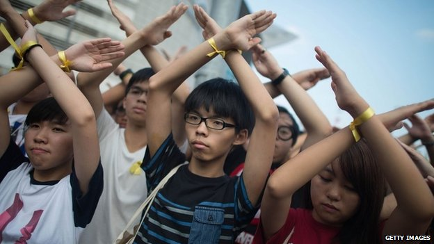 Joshua Wong (centre) makes a cross with his arms at the flag raising ceremony in Hong Kong on 1 Oct 2014