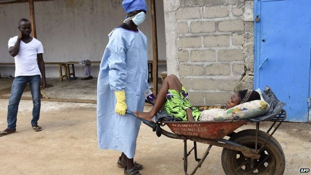 A man pushes a wheelbarrow containing a woman thought to be a victim of the Ebola virus at the Ebola treatment centre at Island Hospital in Monrovia, 2 October 2014