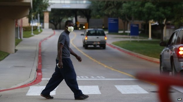 A pedestrian in Dallas takes precautions near the hospital holding Mr Duncan