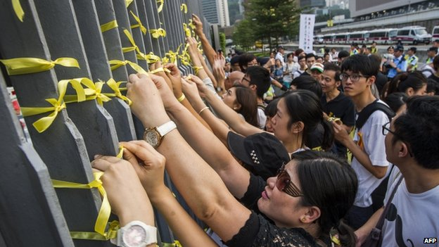 Students in Hong Kong attach yellow ribbons to the barriers fences of government offices as they protest for greater democratic rights on 24 September 2014