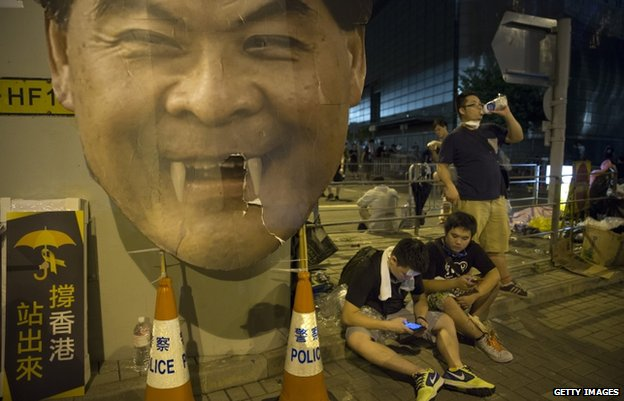 "Protesters gather in the streets outside the Hong Kong Government Complex next to a cardboard poster of C.Y.Leung, Hong Kong""s Chief Executive on 30 September 2014"
