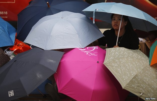 A protester sits under umbrellas as she blocks the main street to the financial Central district outside the government headquarters in Hong Kong, 30 September 2014.